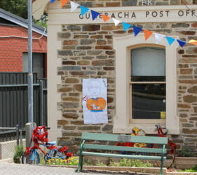 Bike art and poster of Lesley the Postmaster at the Gumeracha Post Office for the Tour Down Under